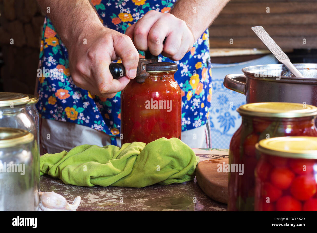 the man closes with jars of pickled tomatoes and a sauce of flour in a rustic kitchen on a summer day Stock Photo