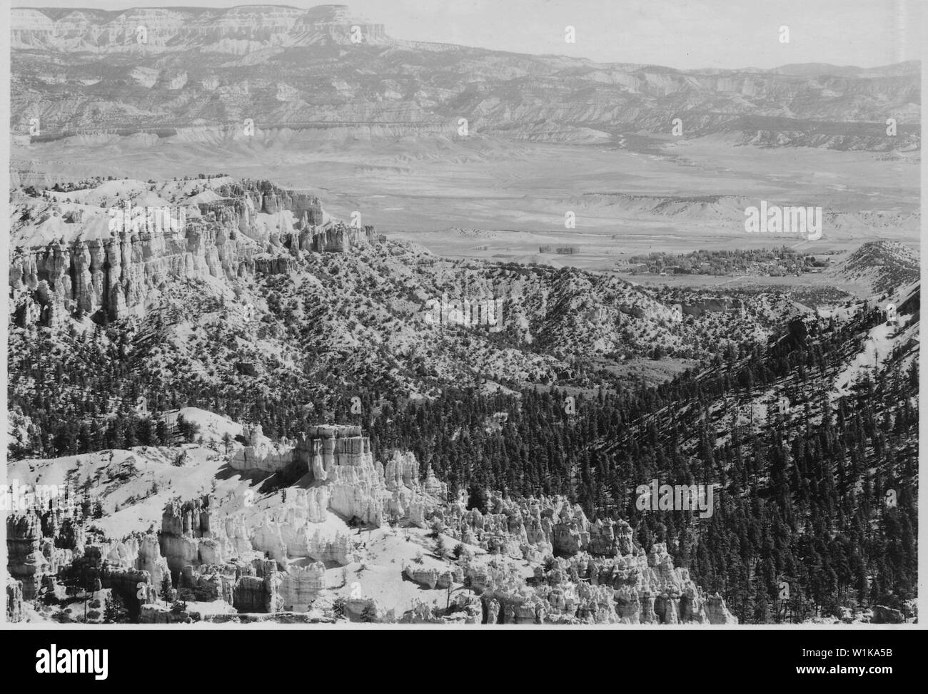 View east from rim near Inspiration Point showing Bryce Temple in the foreground, bottom of the Canyon, village of Tropic, Utah, Valley of the Pahreah River, and Escalante Mountain. Stock Photo