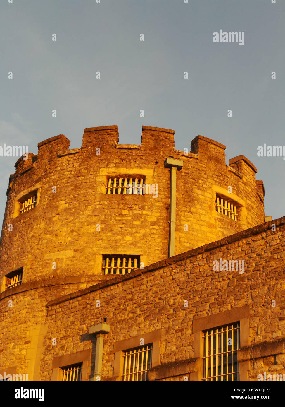 Oxford, United Kingdom - April 06 2013:   The settting sun casts a warm light over the tower of Oxford Castle off Paradise St - Stock Image