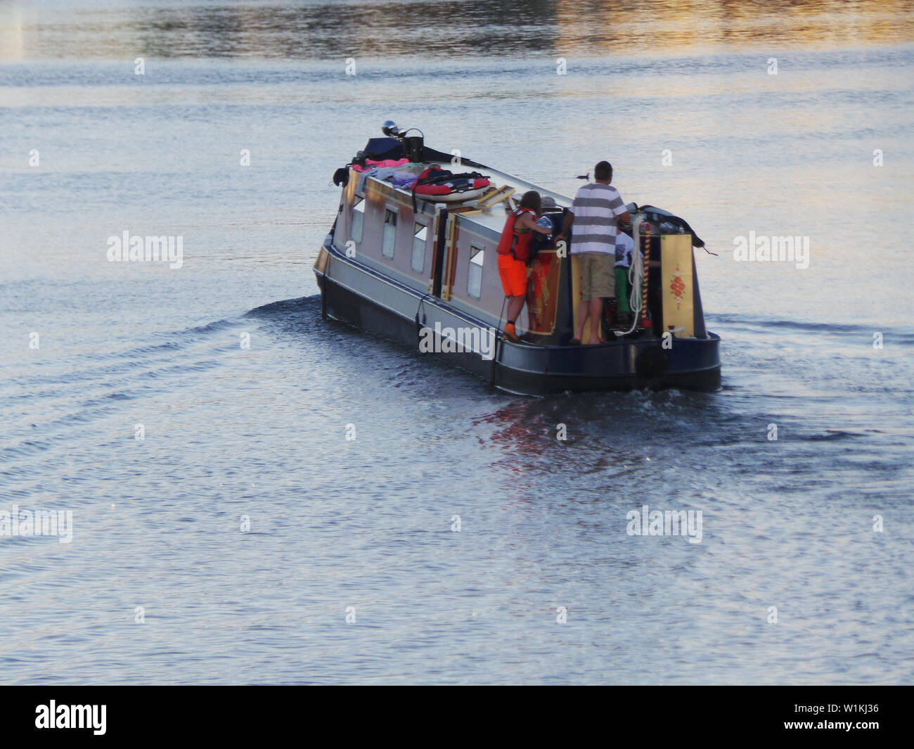 Reading, UK. 30th July 2013. A narrowboat peacefully heads down the River Thames - Stock Image