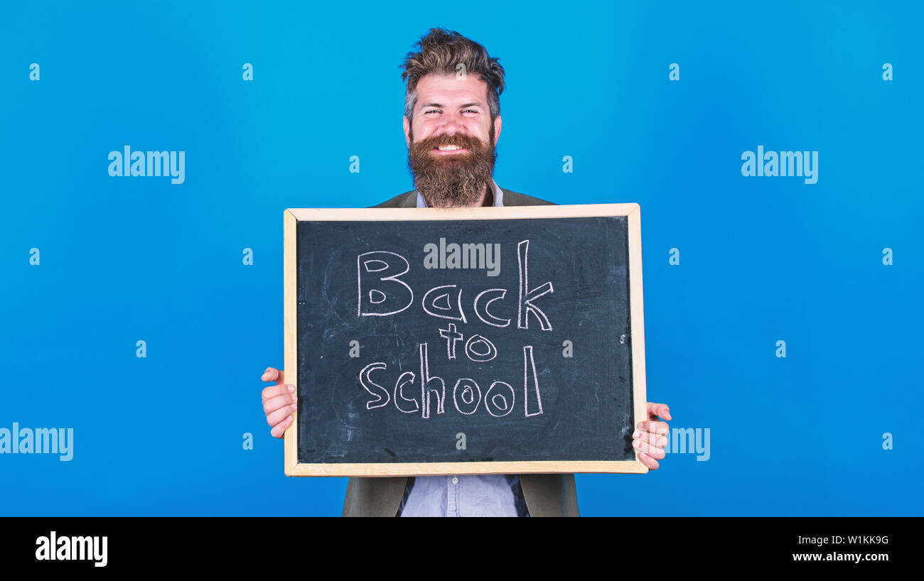 New semester in school. Teacher bearded man stands and holds blackboard with inscription back to school blue background. Teacher invites to continue studying. Continue your education with us. Stock Photo