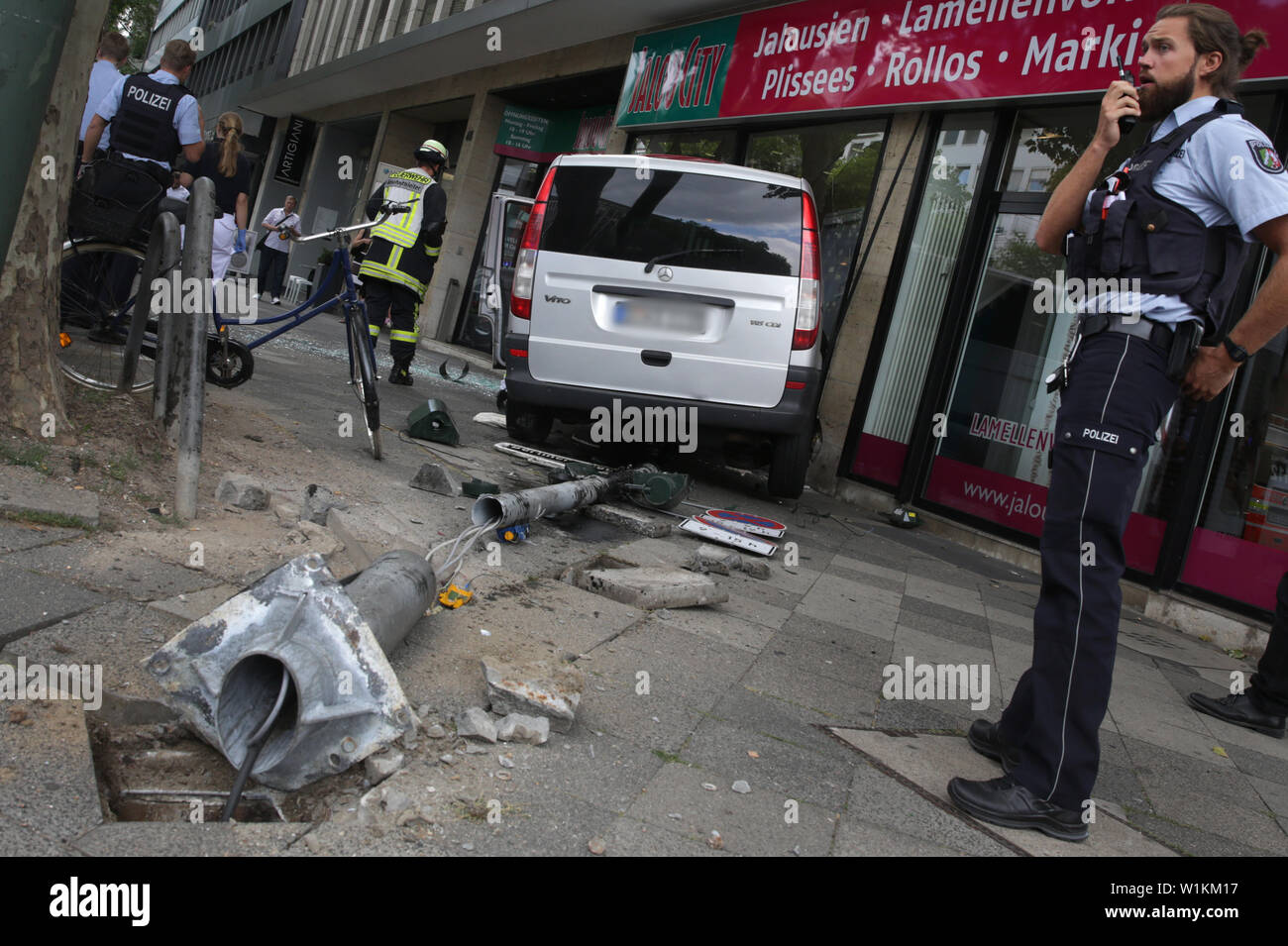 03 July 2019, North Rhine-Westphalia, Duesseldorf: A car is standing in a shop window after an accident in Düsseldorf. For reasons unknown so far, the car in the city centre has gone off the road and driven into a shop window. Photo: Martin Gerten/dpa - ATTENTION: Indicator was pixelated for legal reasons - Stock Image