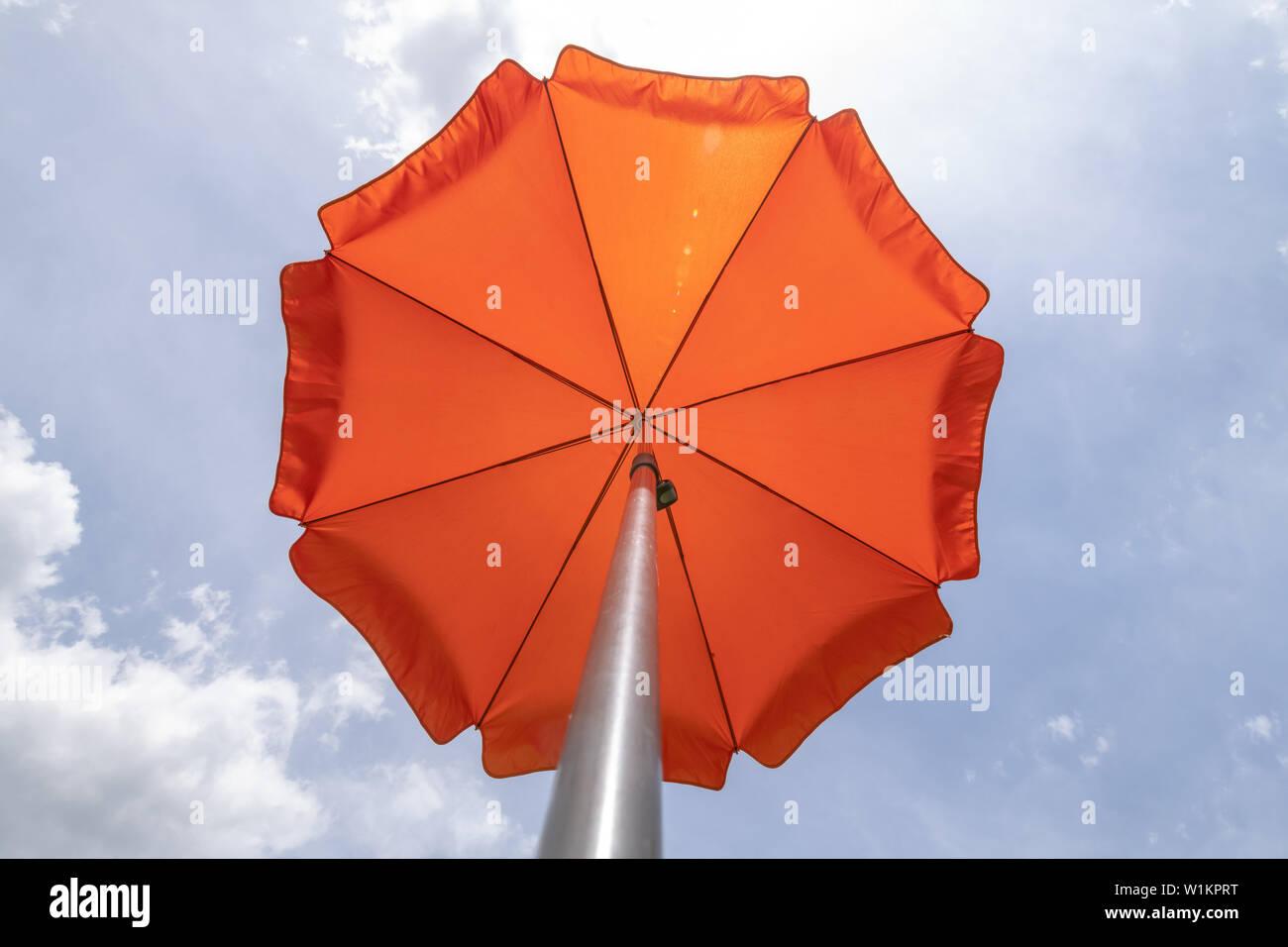 b27af3462 Photo of a beach umbrella on the blue sky,Beach umbrella.One vibrant orange  colored sunshade against vivid blue sky and white cloud.