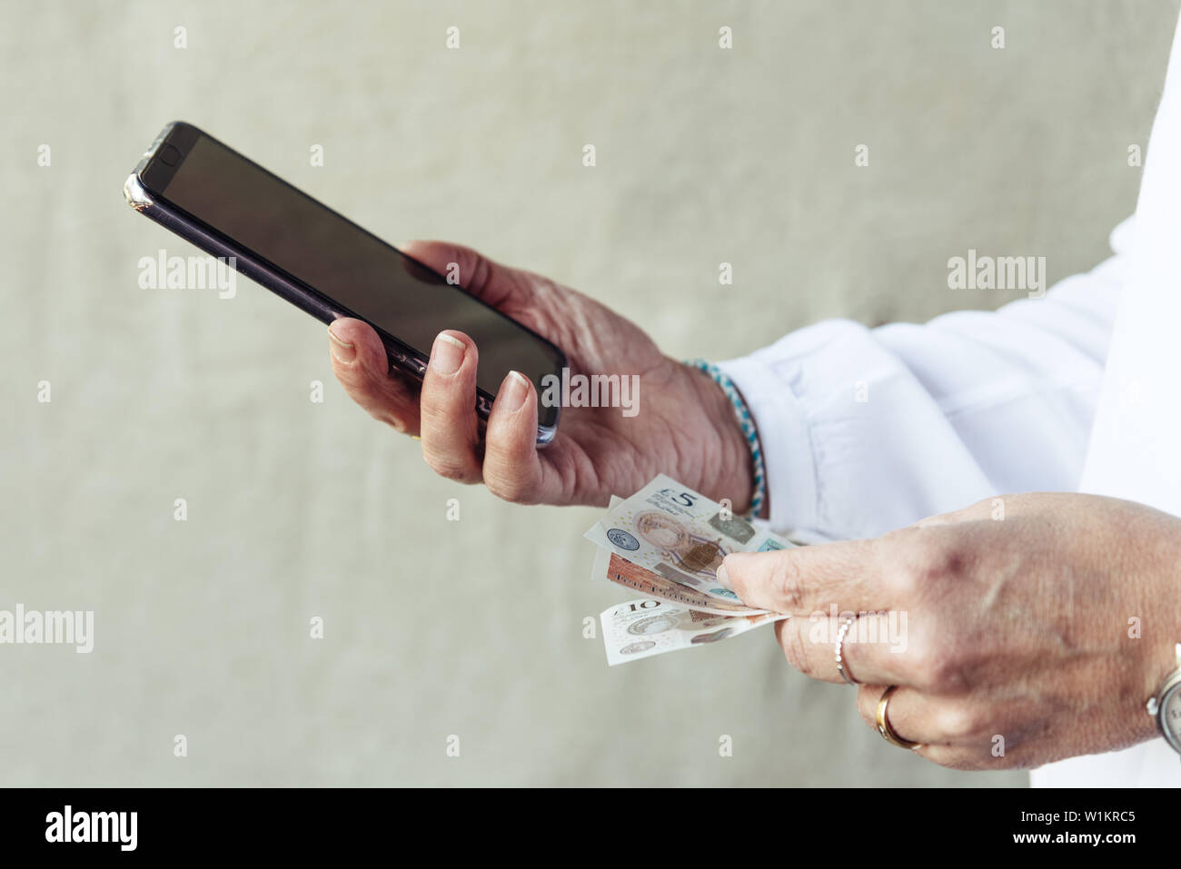Close up of woman hand with smartphone and bank notes.  Business, technology, communication, leisure and e-commerce concept Stock Photo