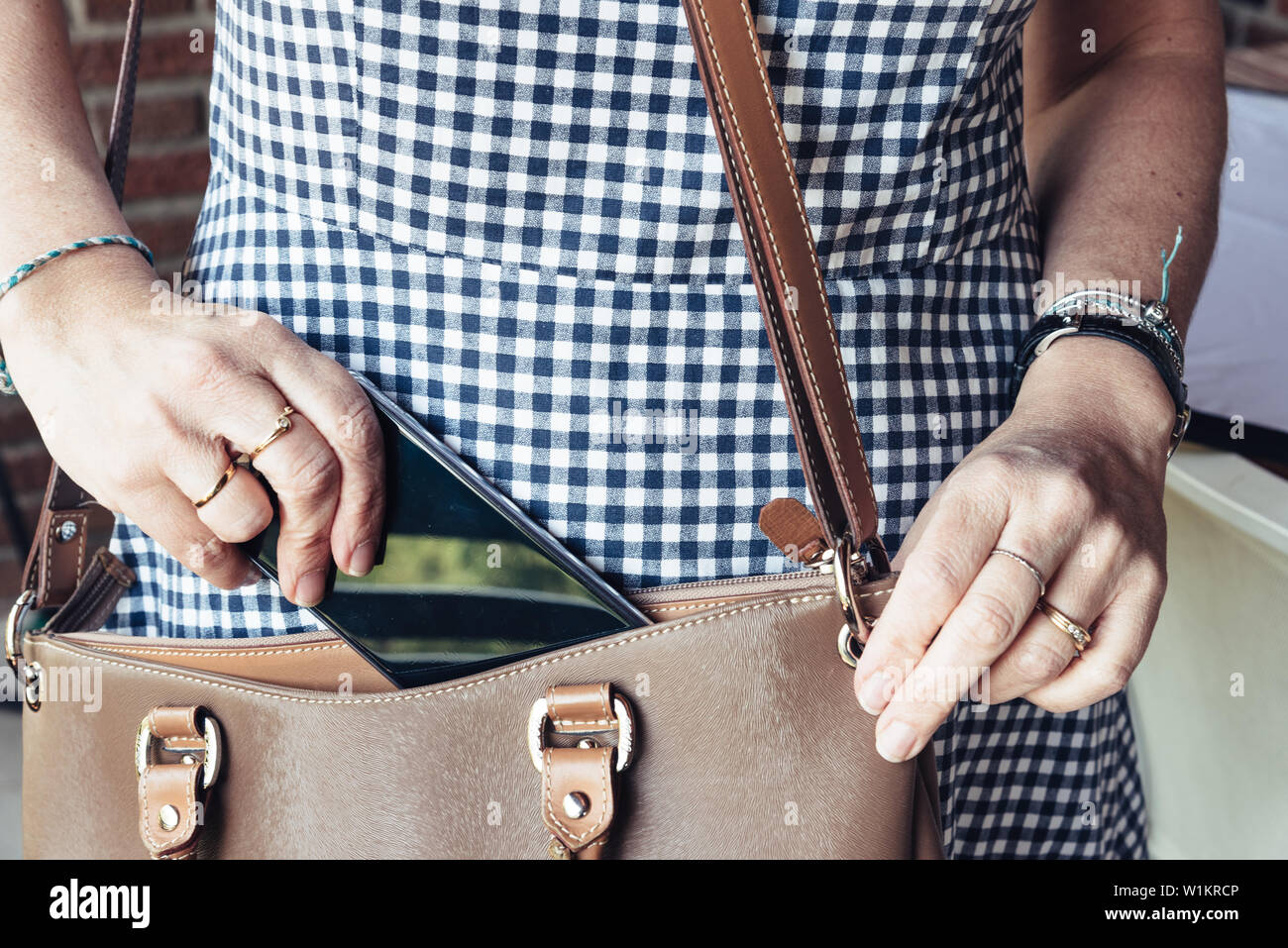 Close up of woman taking out smartphone from bag.  Business, technology, communication, leisure and people concept Stock Photo