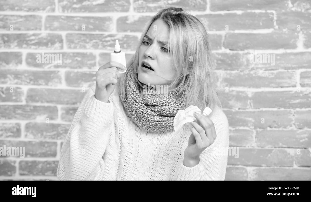 Having blocked nose. Suffering from asthma or allergic rhinitis. Sick woman injecting drops into nose. Cute woman nursing nasal cold or allergy. Pretty girl with runny nose holding nasal drops. Stock Photo