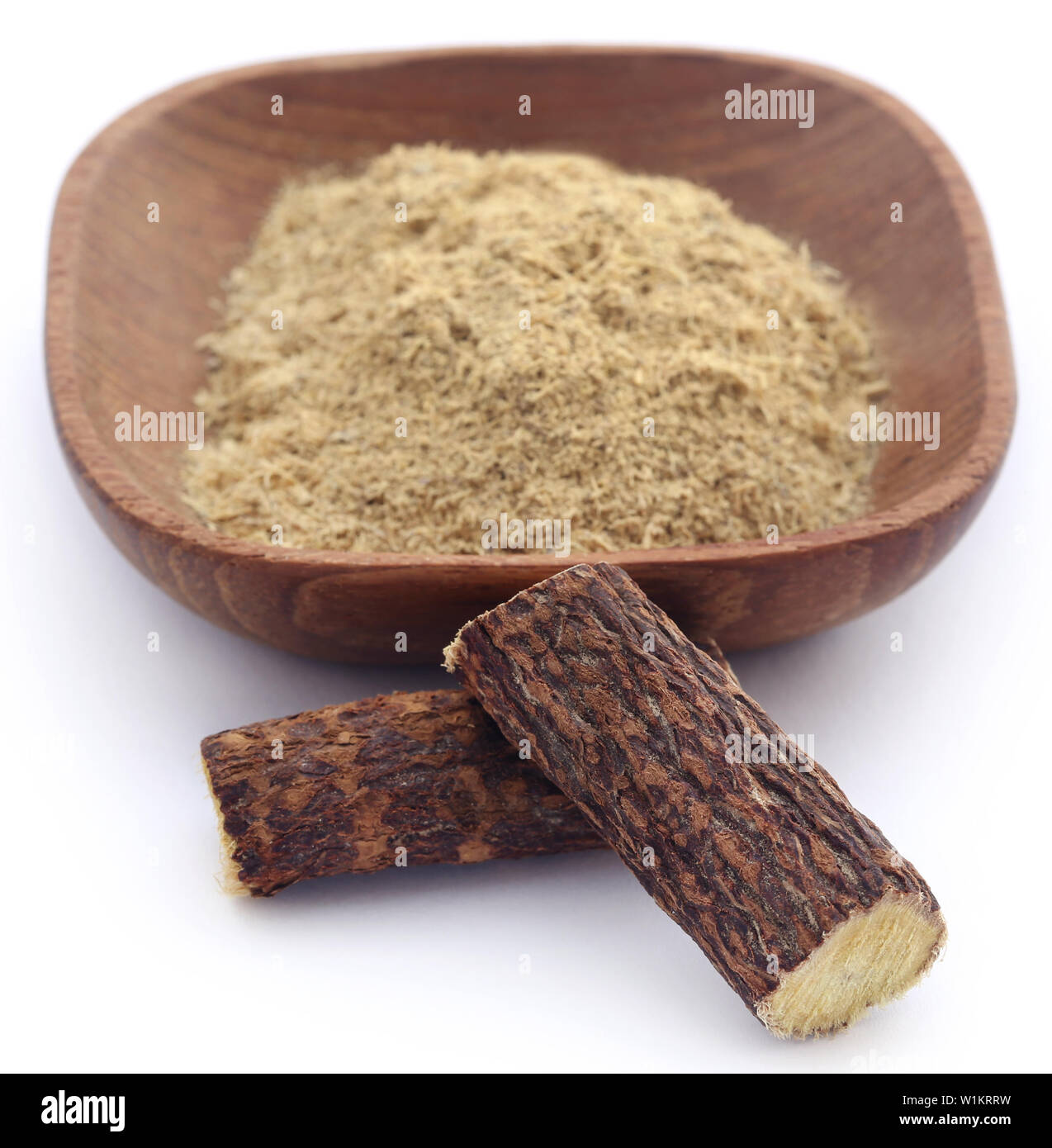 Liquorice stick and ground in a bowl over white - Stock Image