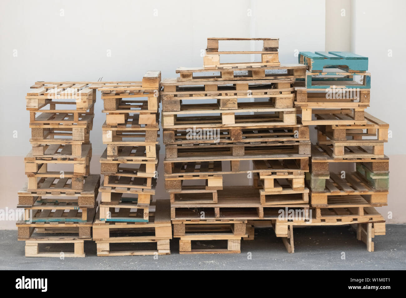 description: Pallets stacked on top of each other on the ground and against a white wall Stock Photo