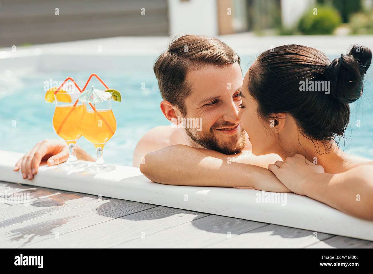 man and a woman look lovingly at each other while in the pool. Goodbye work, hi summer vacation-swimming and tanning Stock Photo