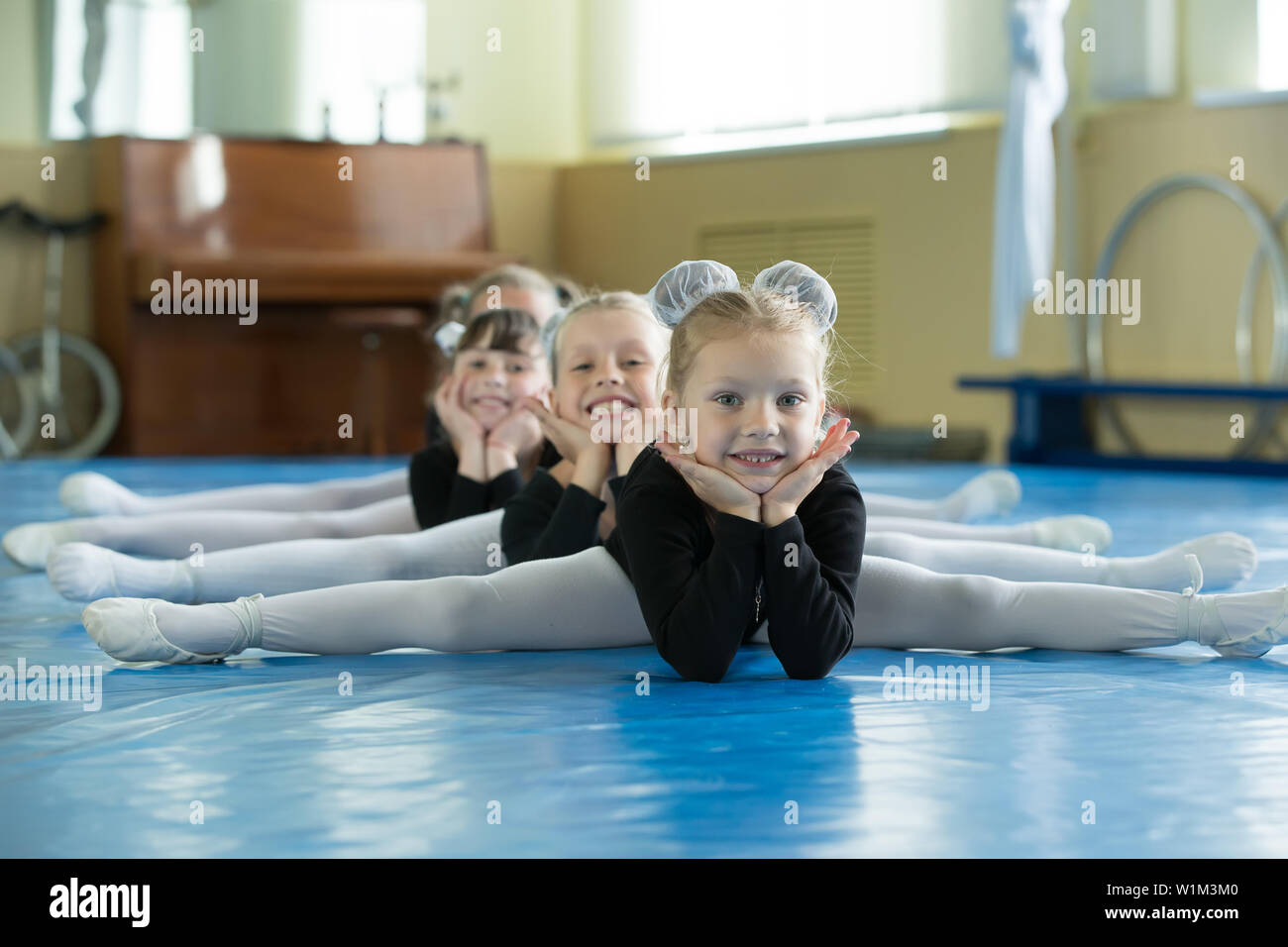 Little girls gymnasts sit on the splits  Children do physical