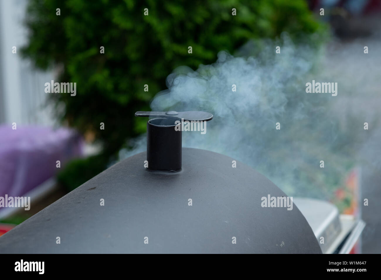 description: Puffy smoke from charcoal chimney starter Stock Photo