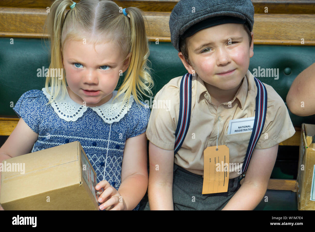Kidderminster, UK. 29th June, 2019. Severn Valley Railways 'Step back to the 1940's' gets off to a fabulous start this weekend with costumed re-enactors playing their part in providing an authentic recreation of wartime Britain. Young evacuee children, wearing name tags, sit waiting at a vintage railway station ready for the journey to their temporary new home in the countryside. Credit: Lee Hudson - Stock Image