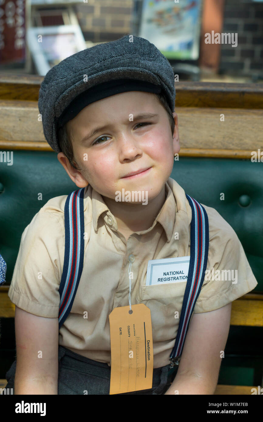 Kidderminster, UK. 29th June, 2019. Severn Valley Railways 'Step back to the 1940's' gets off to a fabulous start this weekend with costumed re-enactors playing their part in providing an authentic recreation of wartime Britain. Anxious, young evacuee boy, wearing braces, flat cap and name tag, sits waiting at a vintage railway station ready for the journey to his temporary new home in the countryside. Credit: Lee Hudson - Stock Image