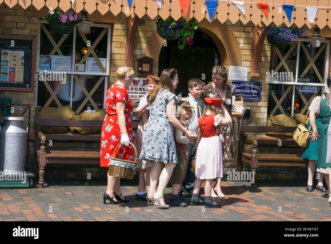 Kidderminster, UK. 29th June, 2019. Severn Valley Railways 'Step back to the 1940's' gets off to a fabulous start this weekend with costumed re-enactors playing their part in providing an authentic recreation of wartime Britain. Evacuee children here being collected at a vintage railway station by their host families. Credit: Lee Hudson - Stock Image