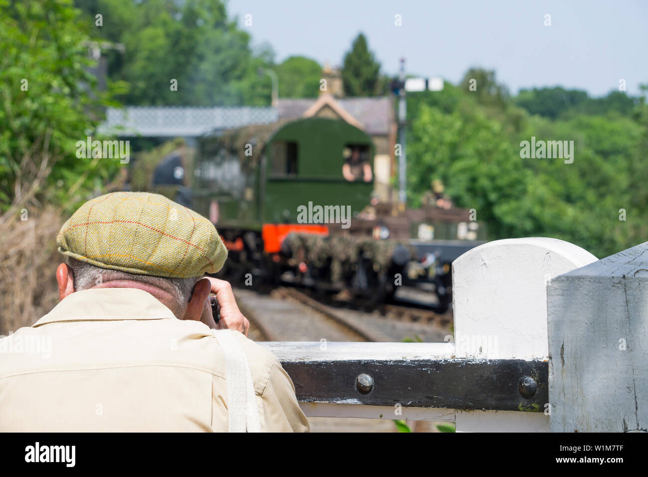 Kidderminster, UK. 29th June, 2019. Severn Valley Railways 'Step back to the 1940's' gets off to a fabulous start this weekend with costumed re-enactors playing their part in providing an authentic recreation of wartime Britain. A senior man in flat cap stands by a vintage railway station gate, photographing the steam train activity. Credit: Lee Hudson - Stock Image