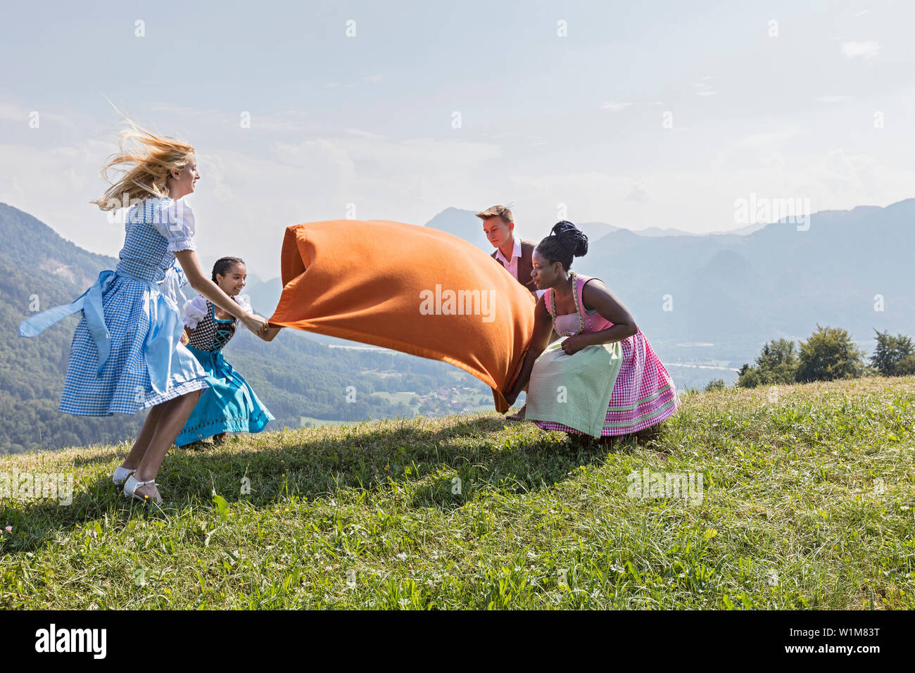 Teenage friends spreading picnic blanket on grass landscape, Bavaria, Germany - Stock Image