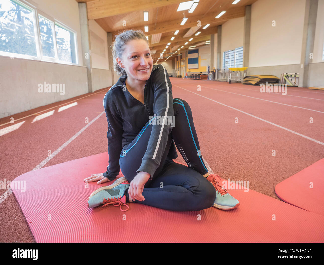 Young woman doing floor exercise in athletics hall on tartan track, Offenburg, Baden-Württemberg, Germany Stock Photo