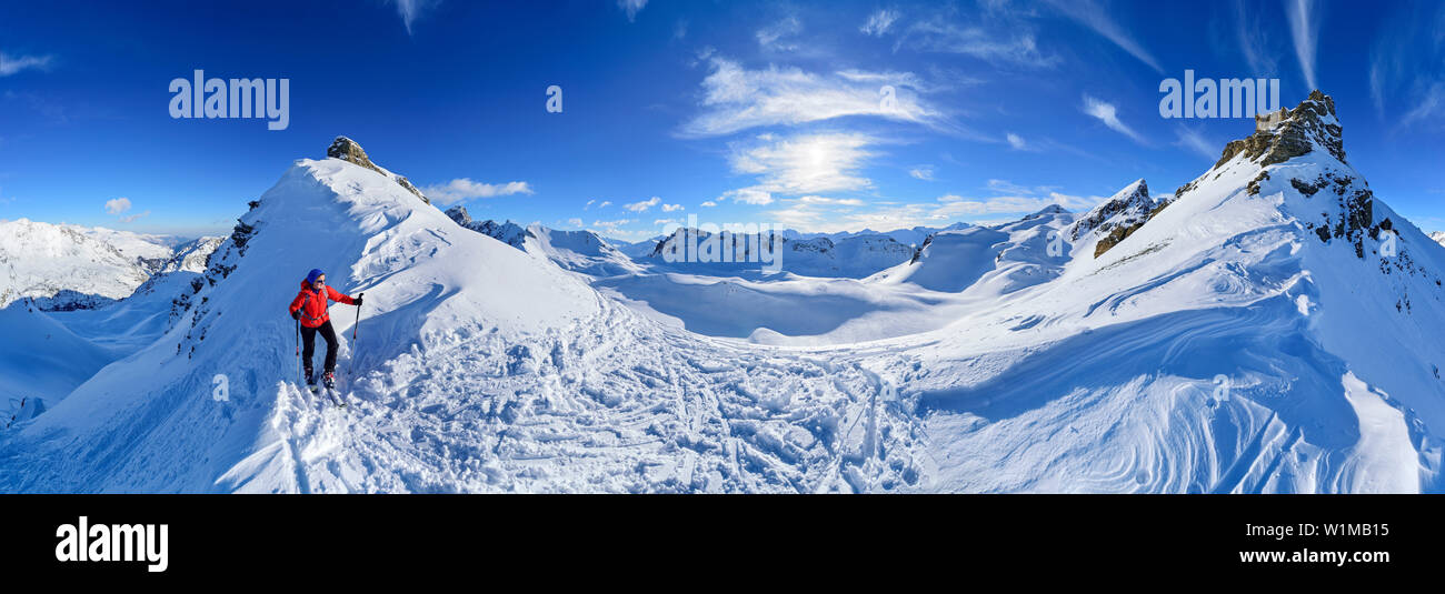 Panorama with woman back-country skiing, view to Monte Soubeyran and Aiguille de Barsin, Monte Soubeyran, Valle Maira, Cottian Alps, Piedmont, Italy - Stock Image