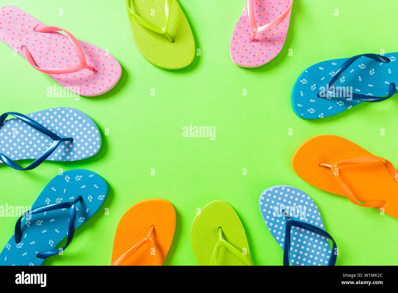 a lot of flip flop colored sandals, summer vacation on colored background, copy space top view. - Stock Image