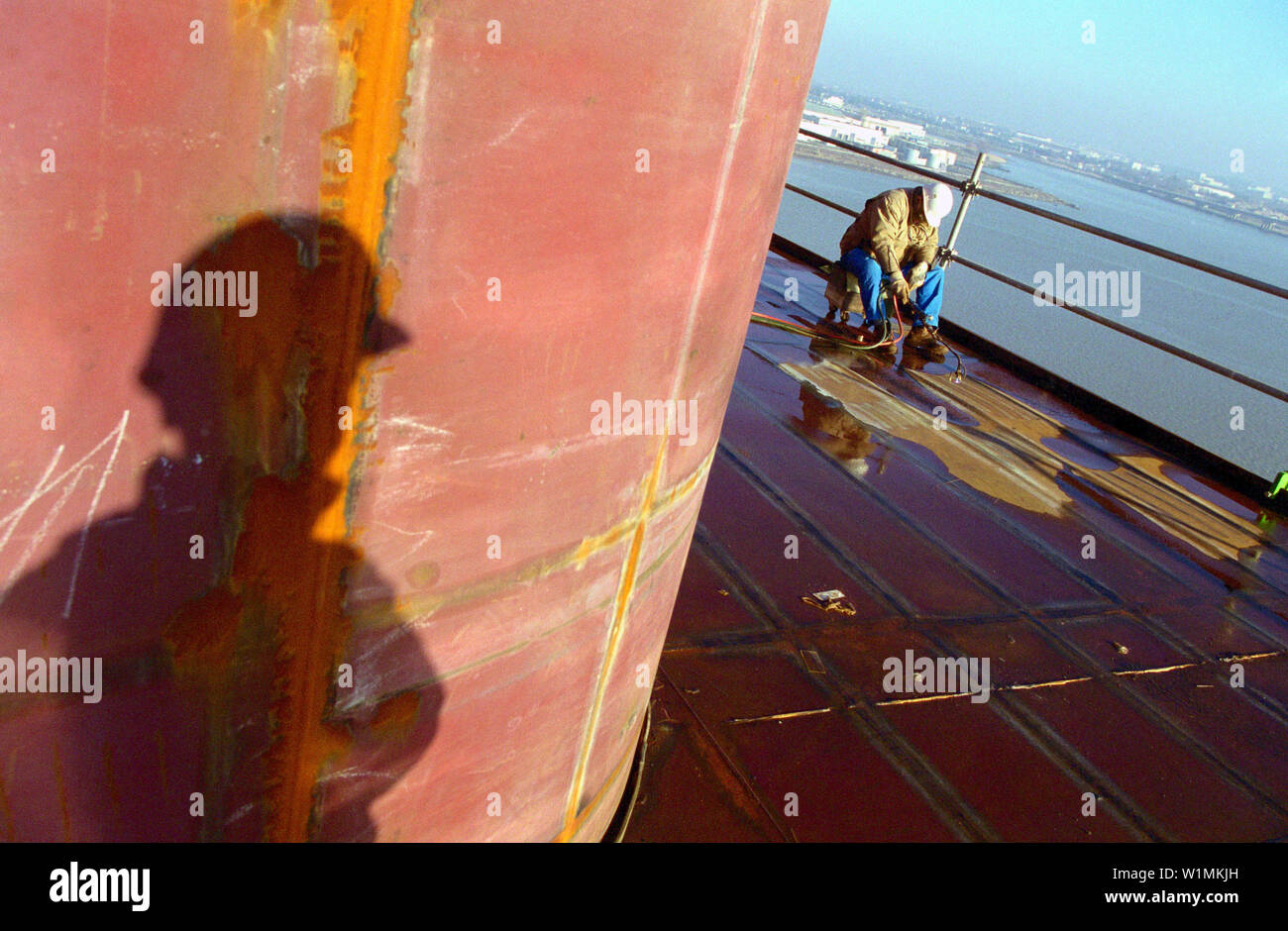 Worker and shadow, dry dock, Queen Mary 2, Saint-Nazaire, France - Stock Image
