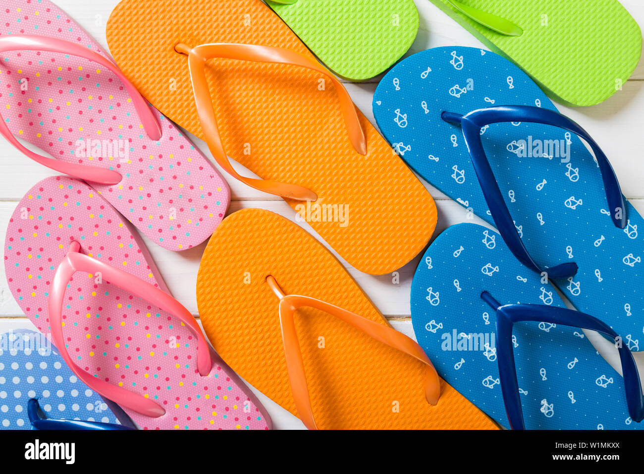 a lot of flip flop colored sandals, summer vacation on wooden background, copy space top view. - Stock Image