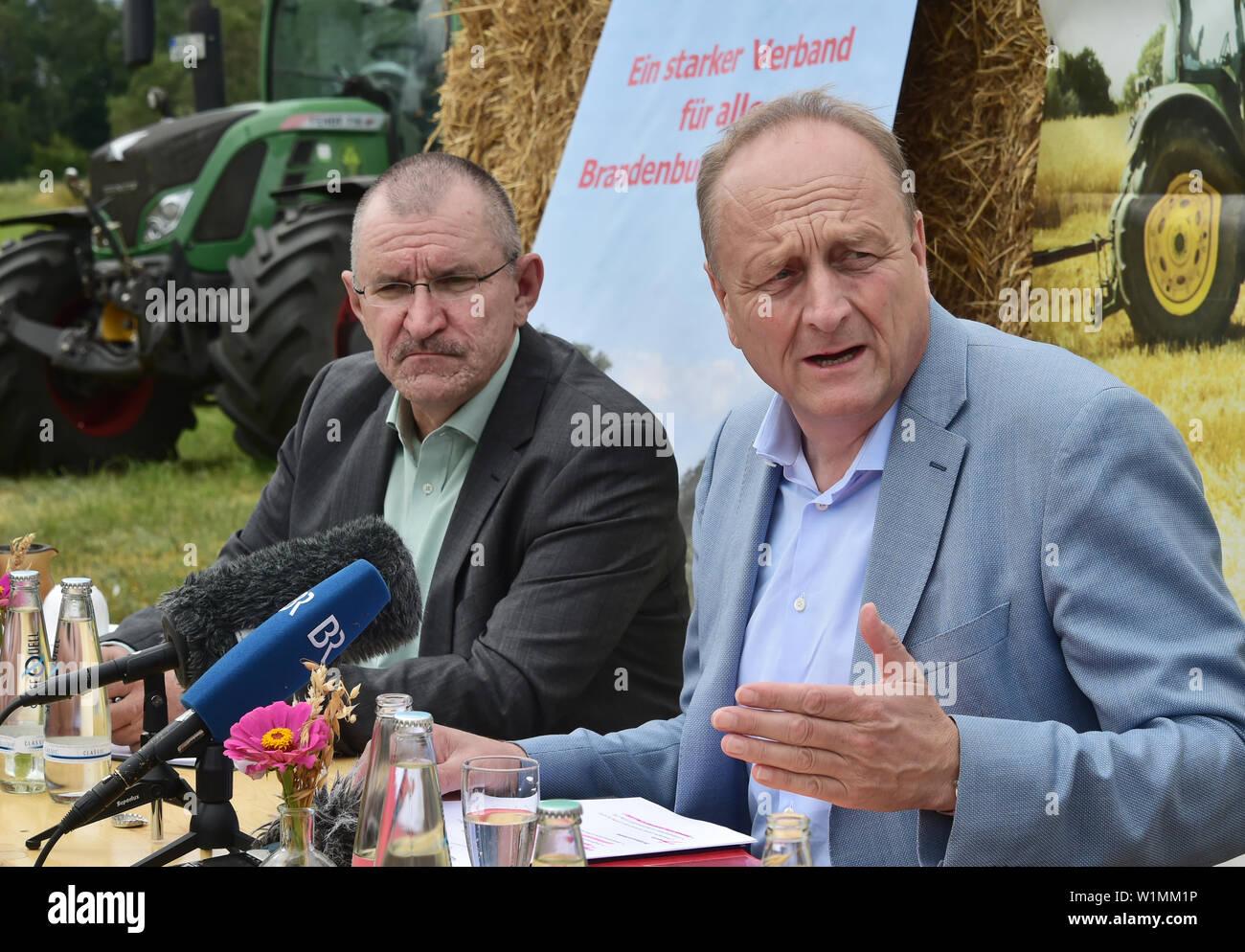 03 July 2019, Brandenburg, Dallgow-Döberitz: Joachim Rukwied (r), President of the German Farmers' Association, and Henrik Wendorff, President of the Brandenburg State Farmers' Association, speak at the press conference on the start of the harvest. Late frosts and drought are expected to cause large crop losses. Photo: Bernd Settnik/dpa-Zentralbild/dpa - Stock Image