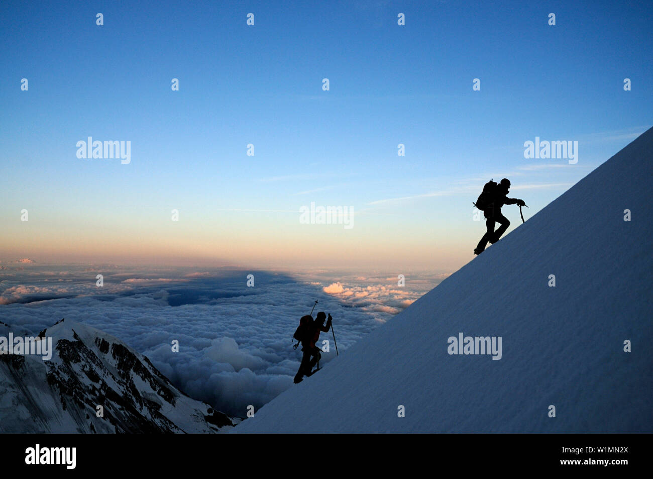 Mountaineers in the shadow of Mont Blanc during ascent of Aiguille de Bionnassay, Mont Blanc, France - Stock Image