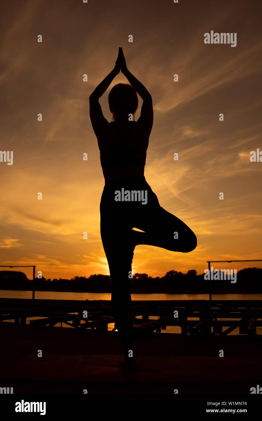 Woman practicing yoga in sunset. Vriksasana, Tree pose Stock Photo