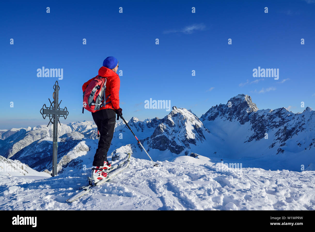 Woman back-country skiing standing at summit of Monte Soubeyran and looking towards Aiguille Jean Coste, Monte Soubeyran, Valle Maira, Cottian Alps, P - Stock Image