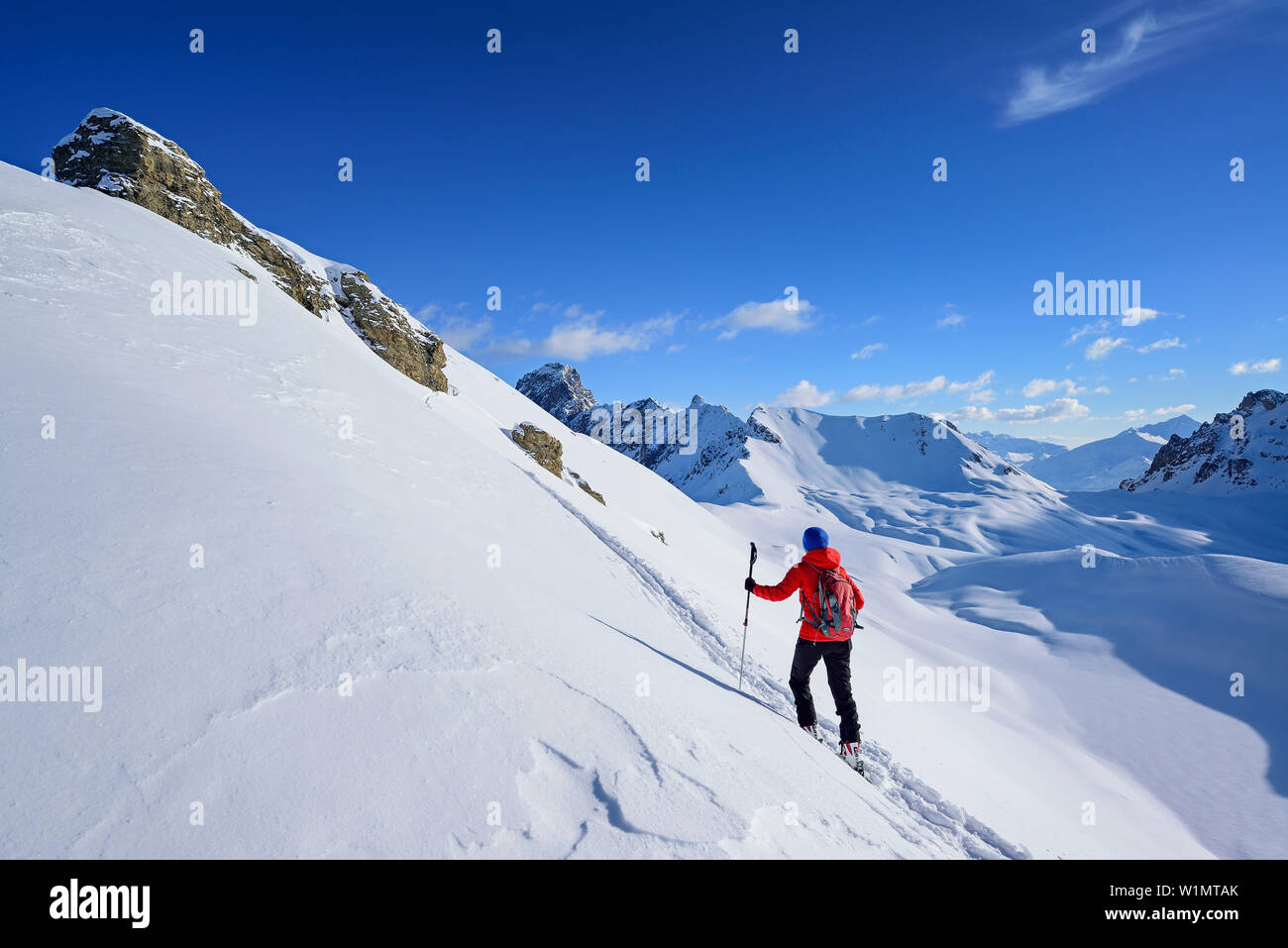 Woman back-country skiing ascending towards Monte Soubeyran, in background Aiguille Jean Coste, Monte Soubeyran, Valle Maira, Cottian Alps, Piedmont, - Stock Image