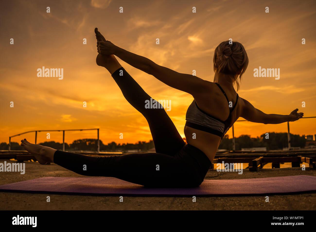 Woman practicing yoga in sunset. Padangusthasana, Dancing Shiva Pose - Stock Image