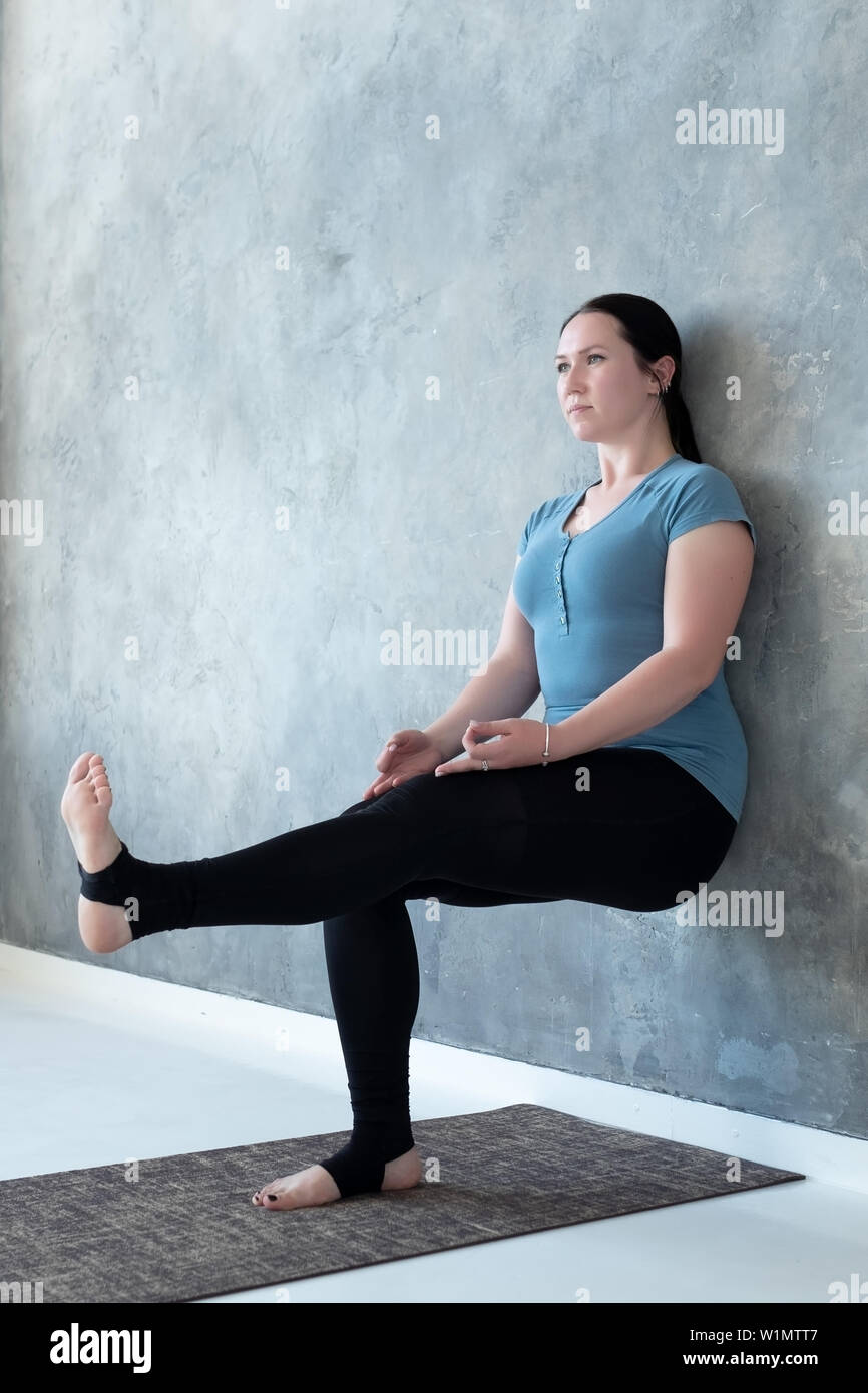 Woman practicing yoga standing in Utkatasana Chair pose near wall raising leg up - Stock Image