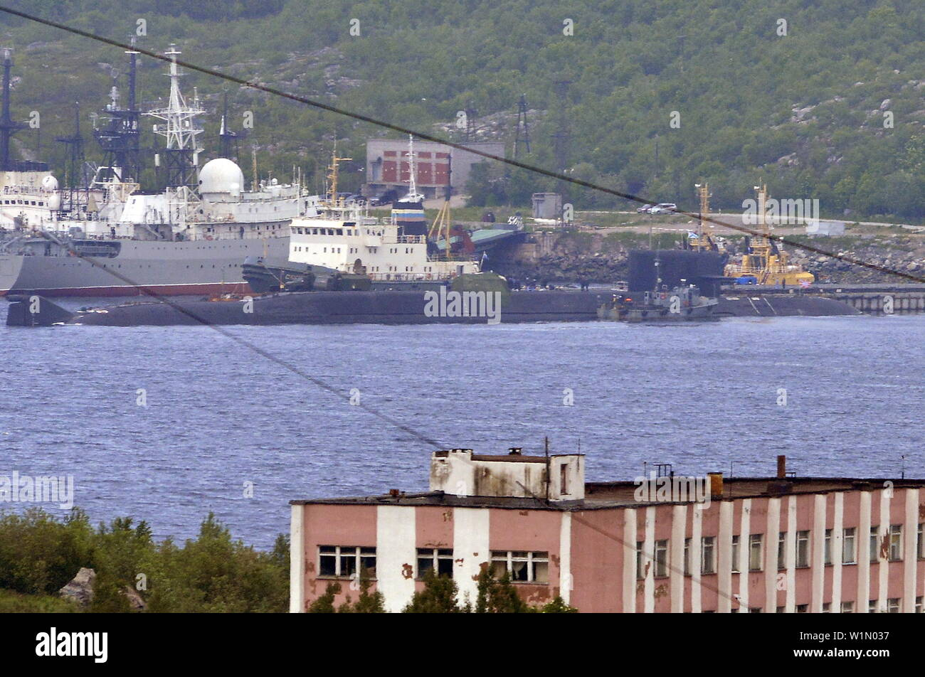 SEVEROMORSK, RUSSIA – JULY 3, 2019: A rescue tugboat (back) and the BS-136 Orenburg ballistic missile submarine (front) carrying a nuclear deepwater station of Project 10831 at the Russian Northern Fleet's base. Lev Fedoseyev/TASS - Stock Image