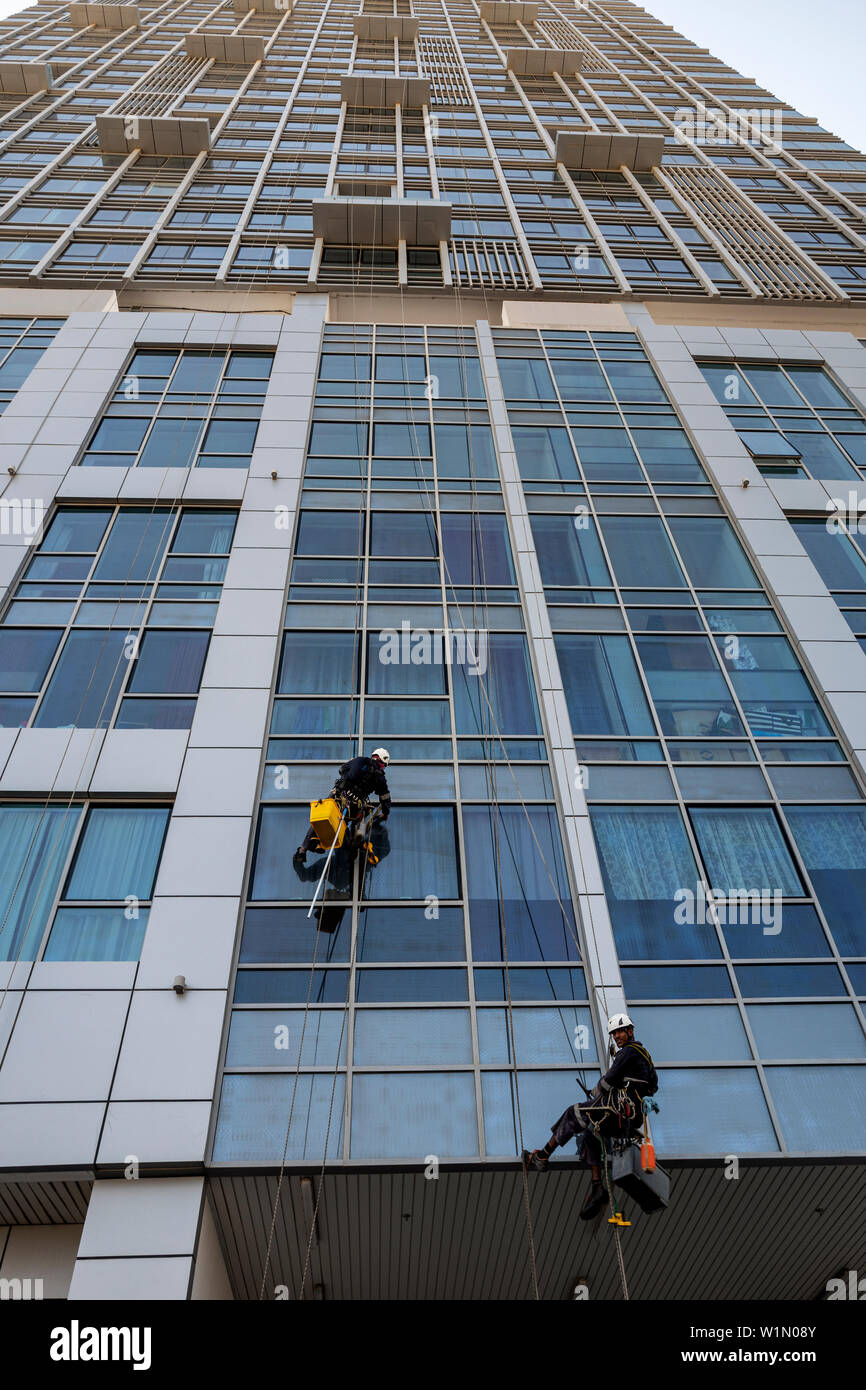 Cleaning windows on a high rise building using ropes and abseiling equipment on Al Reem Island in Abu Dhabi, UAE - Stock Image
