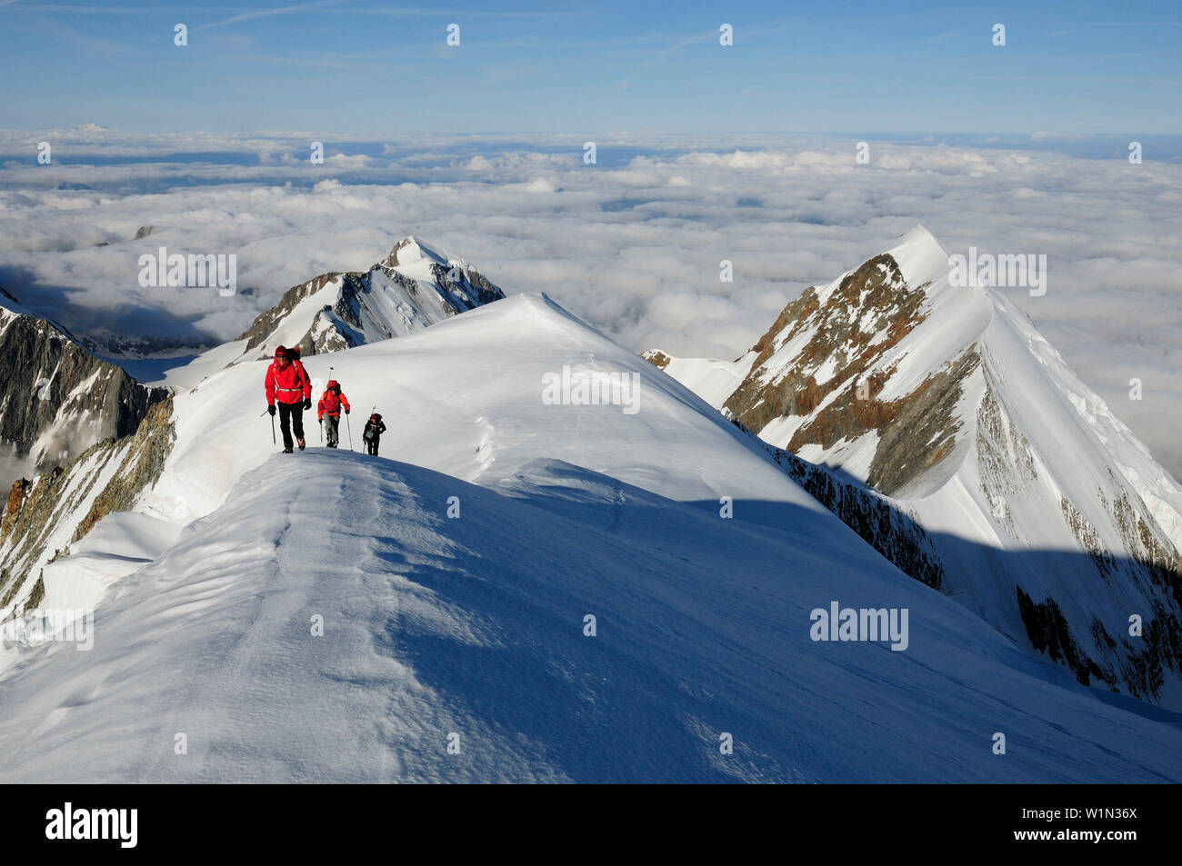 Mountaineers during ascent of Dome de Gouter, Aiguille de Bionnassay in the background, Mont Blanc, France - Stock Image