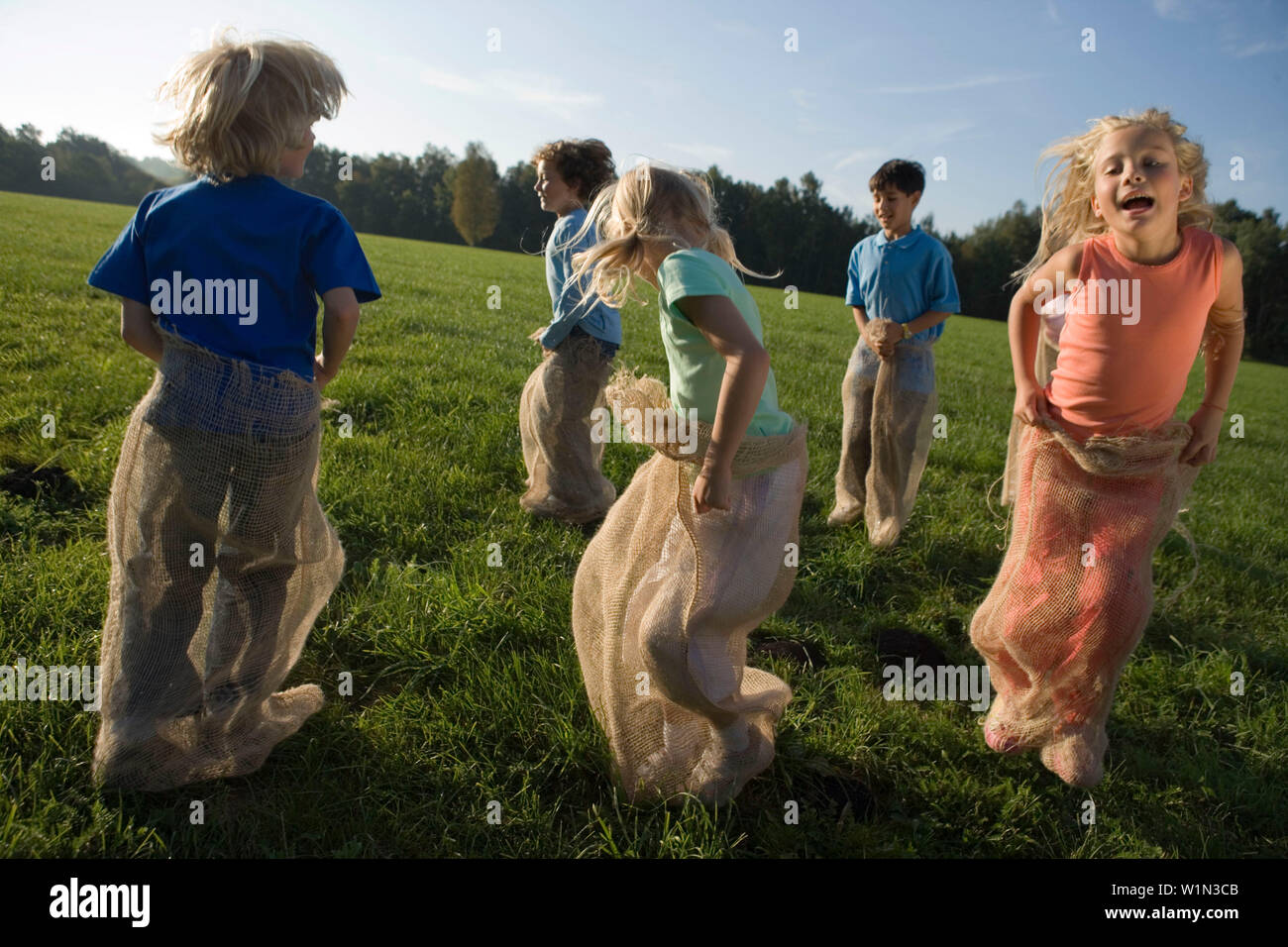 Group of children having a sack race, children's birthday party - Stock Image
