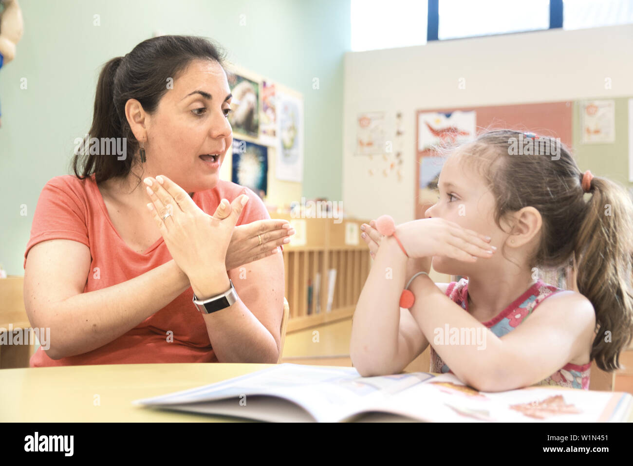 Sign language teacher in a extra tutoring class with a deaf child girl using American Sign Language. - Stock Image