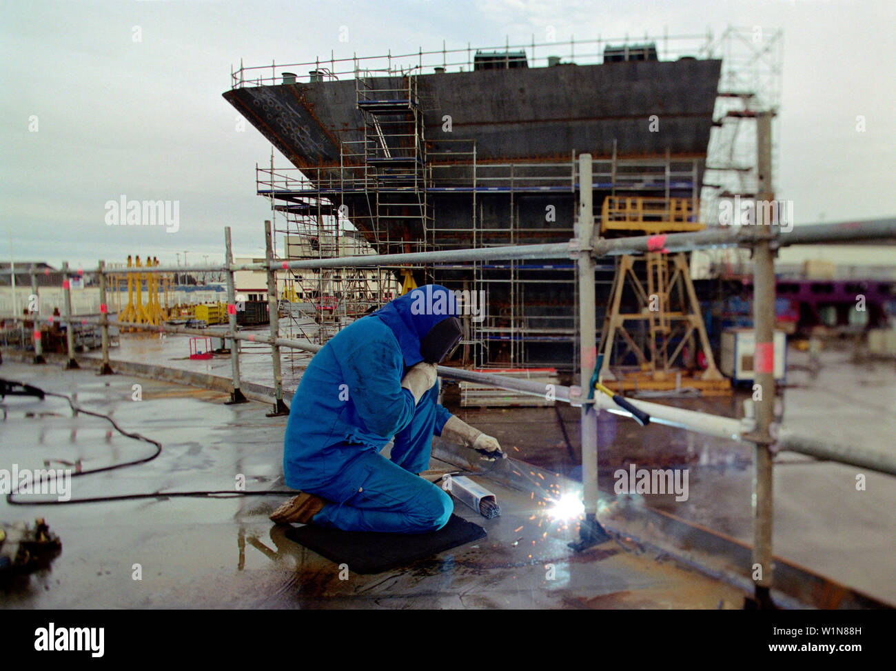 Worker welding steel plates, dry dock, Queen Mary 2, Saint-Nazaire, France - Stock Image