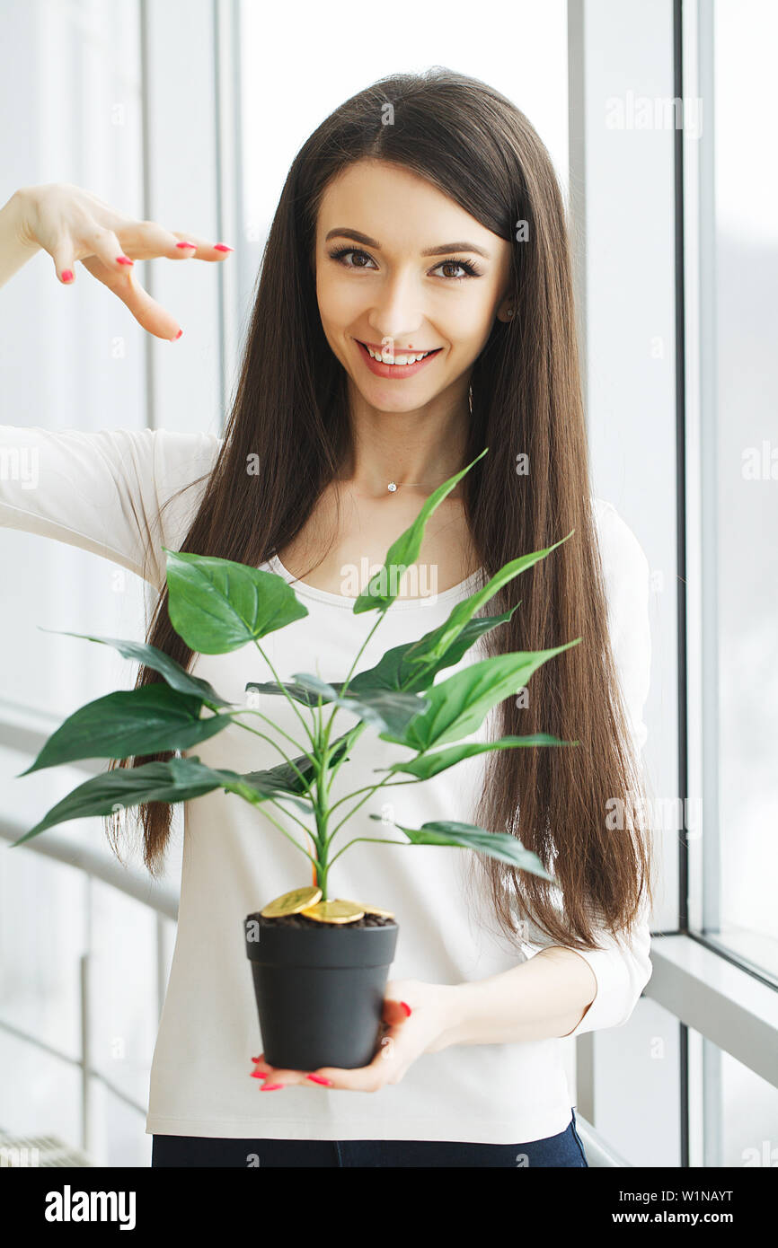 Woman holding, house plant with coins of bitcoin on the ground - Stock Image
