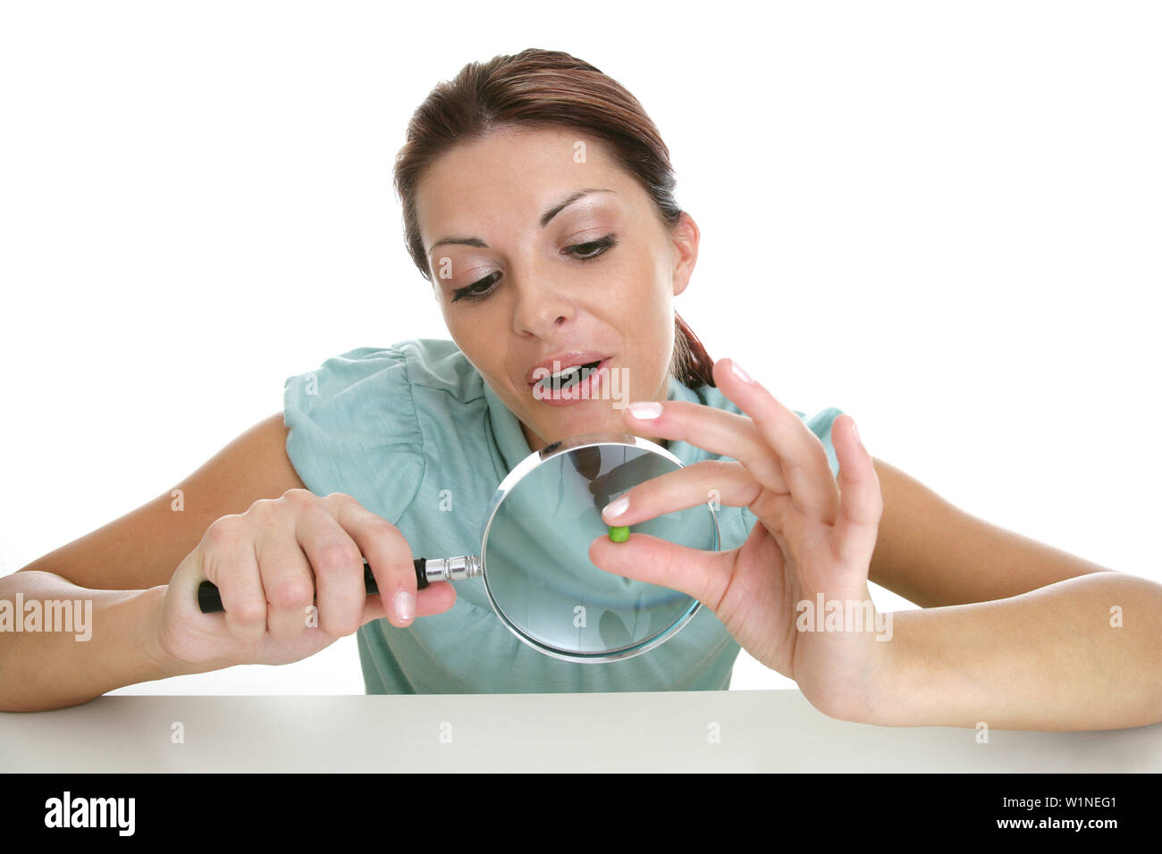 Woman observing pea with magnifying glass, Styria, Austria - Stock Image
