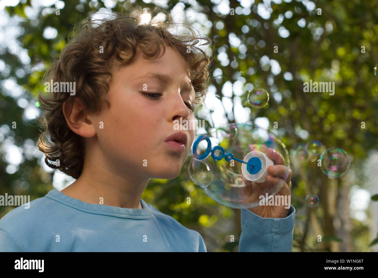 Boy blowing soap bubbles, children's birthday party - Stock Image