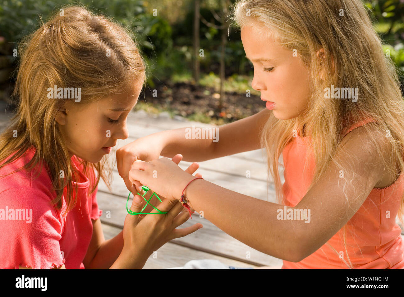 Two girls playing cat's cradle, children's birthday party - Stock Image