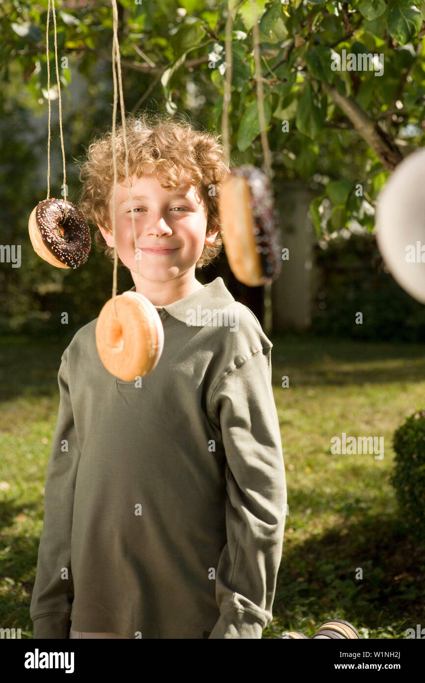 Boy laughing, donut hanging in the near, children's birthday party - Stock Image