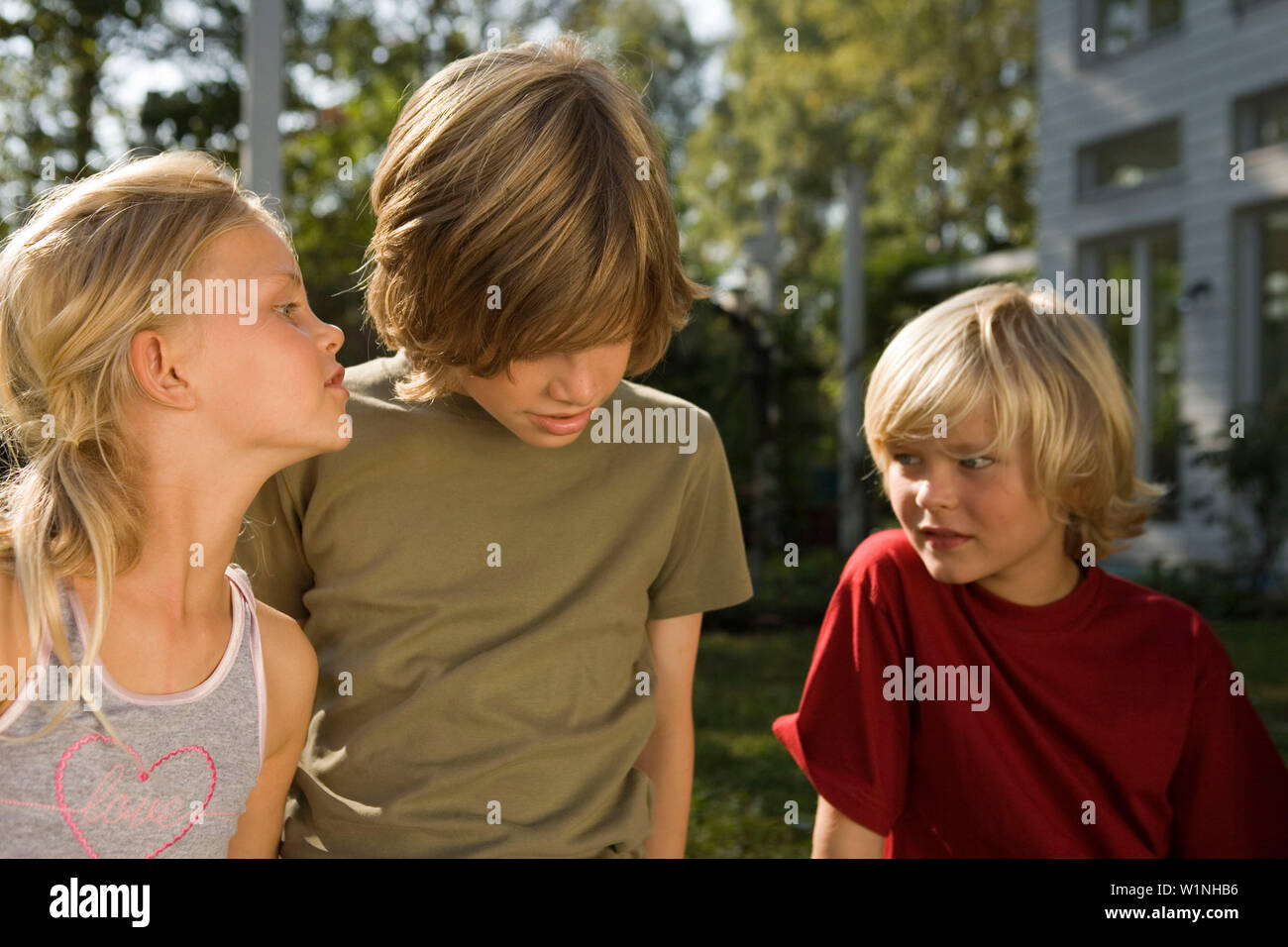 Children playing Chinese whisper, children's birthday party - Stock Image