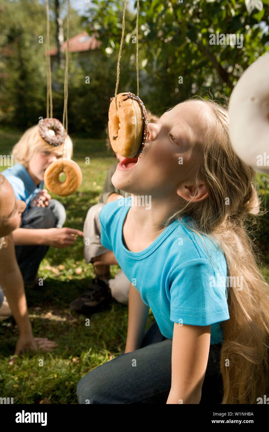 Girls playing donut catching, children's birthday party - Stock Image