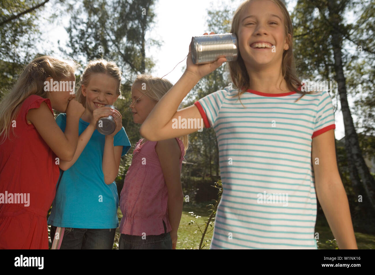 Four girls playing with a tin can phone, children's birthday party - Stock Image