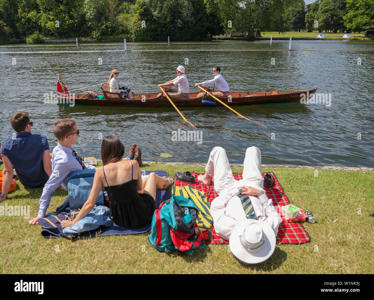 A rowing boat passes spectators on the river bank on the opening day of the 2019 Henley Royal Regatta alongside the river Thames. - Stock Image