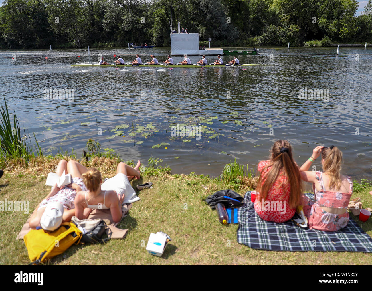 Women watch rowers from the river bank on the opening day of the 2019 Henley Royal Regatta alongside the river Thames. - Stock Image