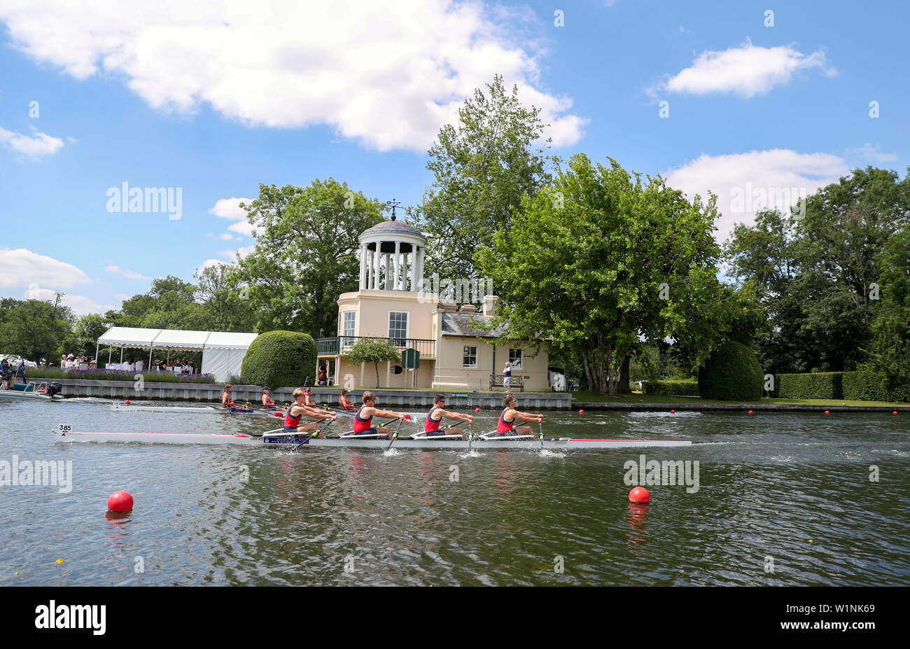 Rowers pass Temple Island on the opening day of the 2019 Henley Royal Regatta alongside the river Thames. - Stock Image