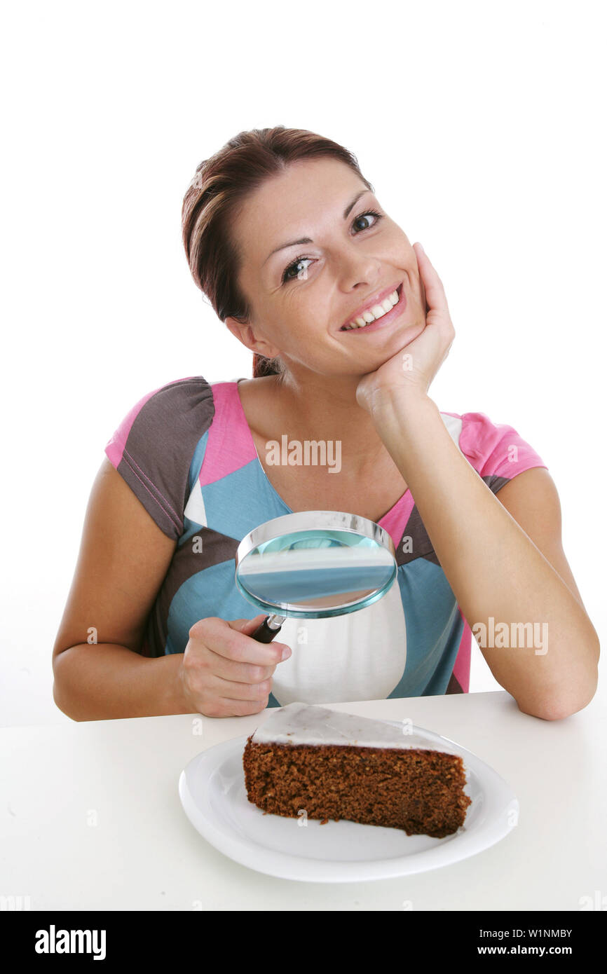 Woman observing chocolate cake through magnifying glass, Styria, Austria - Stock Image
